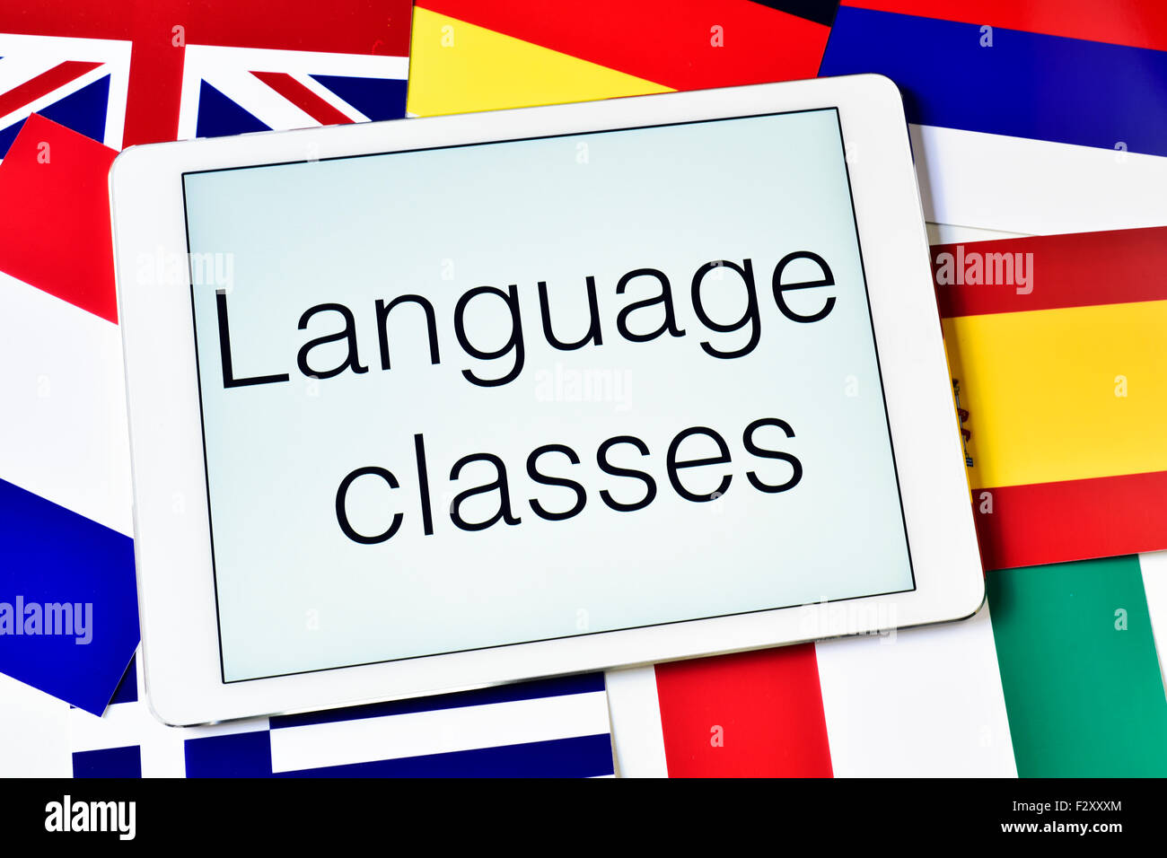 the text language classes in the screen of a tablet computer surrounded by flags of different countries - Stock Image