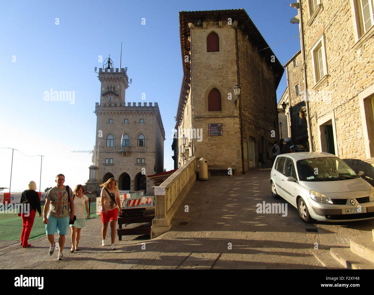 Tourists walk around the Piazza Liberta in the centre of San Marino, with the government palace pictured back left, - Stock Image