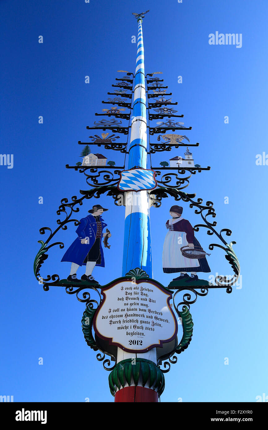 Traditional Bavarian town Maypole Maibaum in classic stripes with figurines. - Stock Image