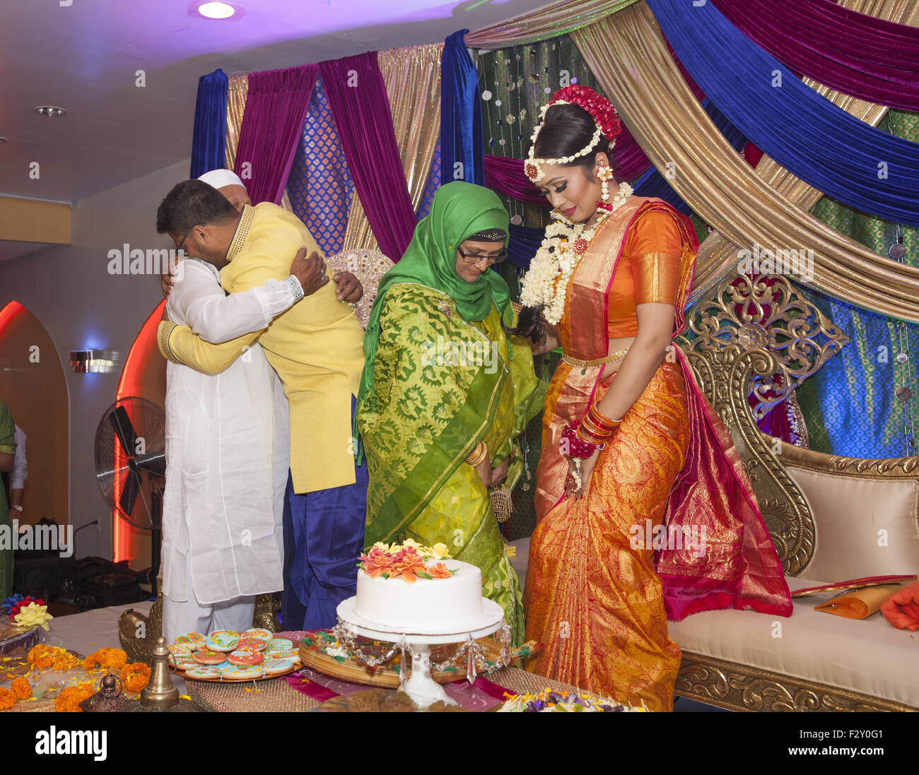 Bangladeshi Muslim couple at their wedding reception greeting the parents of the groom. - Stock Image