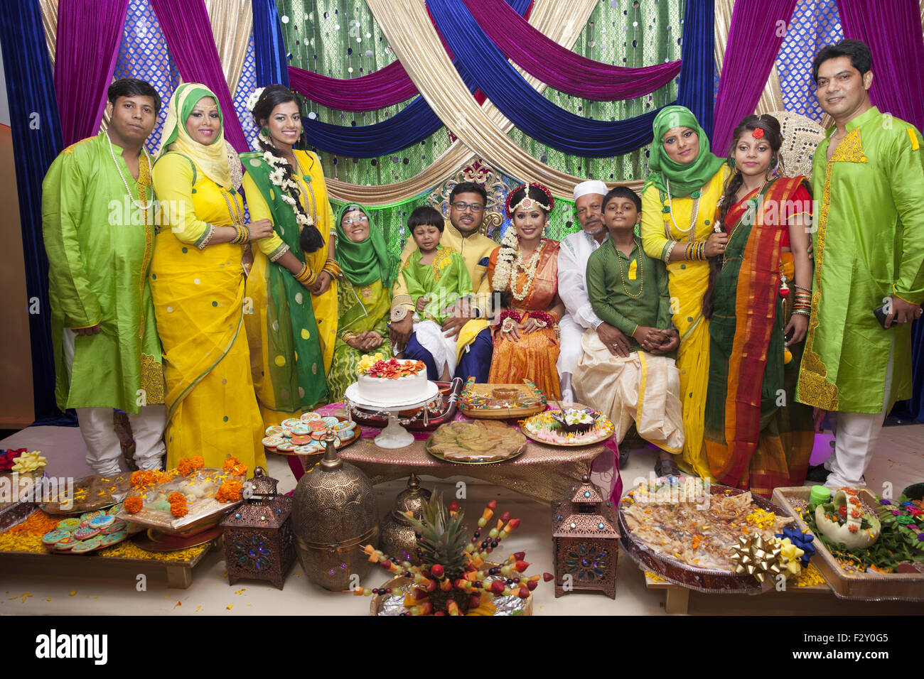 Bangladeshi bride and groom (center) with the groom's family at their wedding reception in Brooklyn,NY - Stock Image