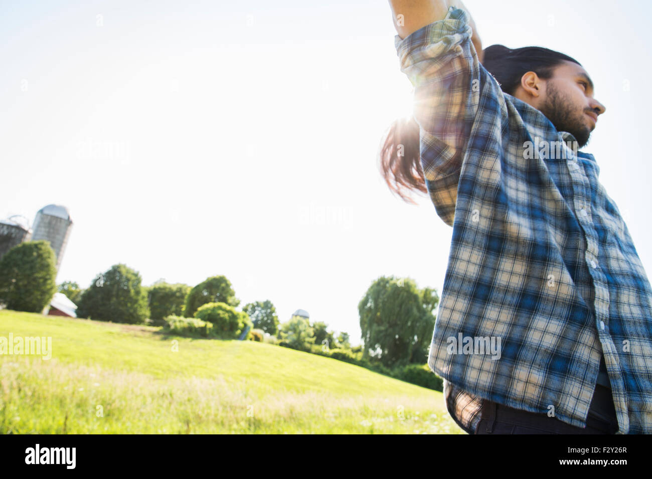 A young man letting down his very long dark hair. - Stock Image