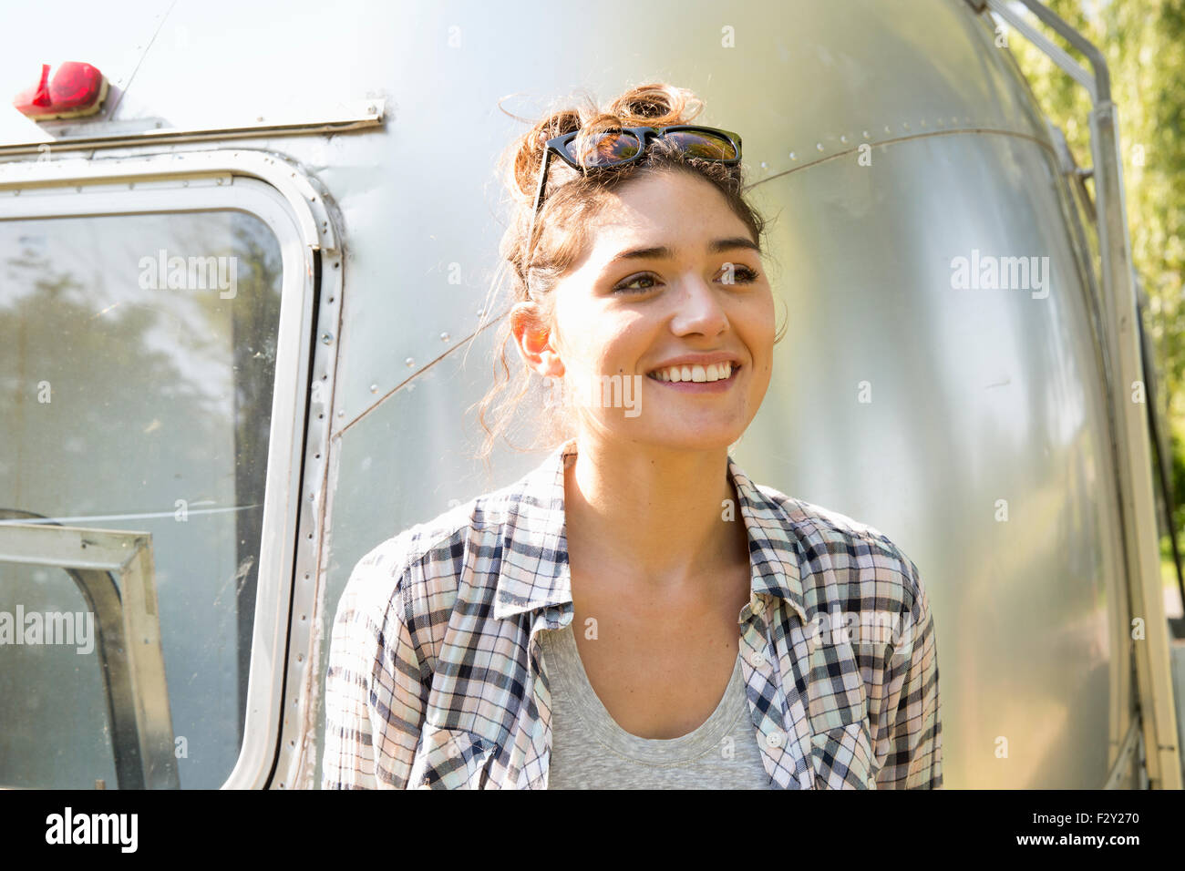A young woman wearing sunglasses by a silver coloured trailer. - Stock Image
