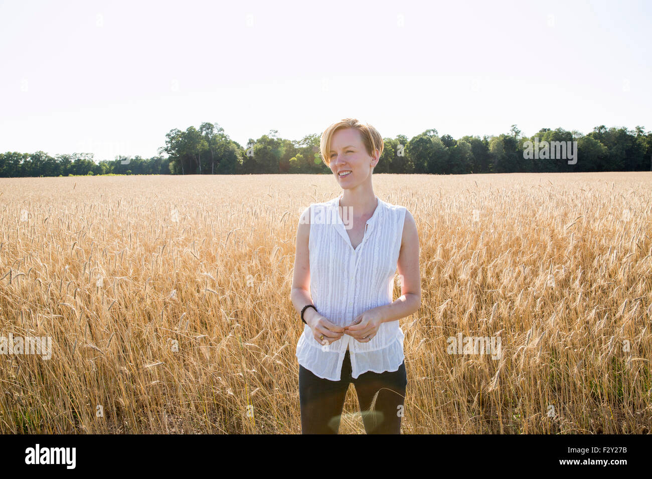 Half length portrait of a young woman standing in a cornfield. - Stock Image