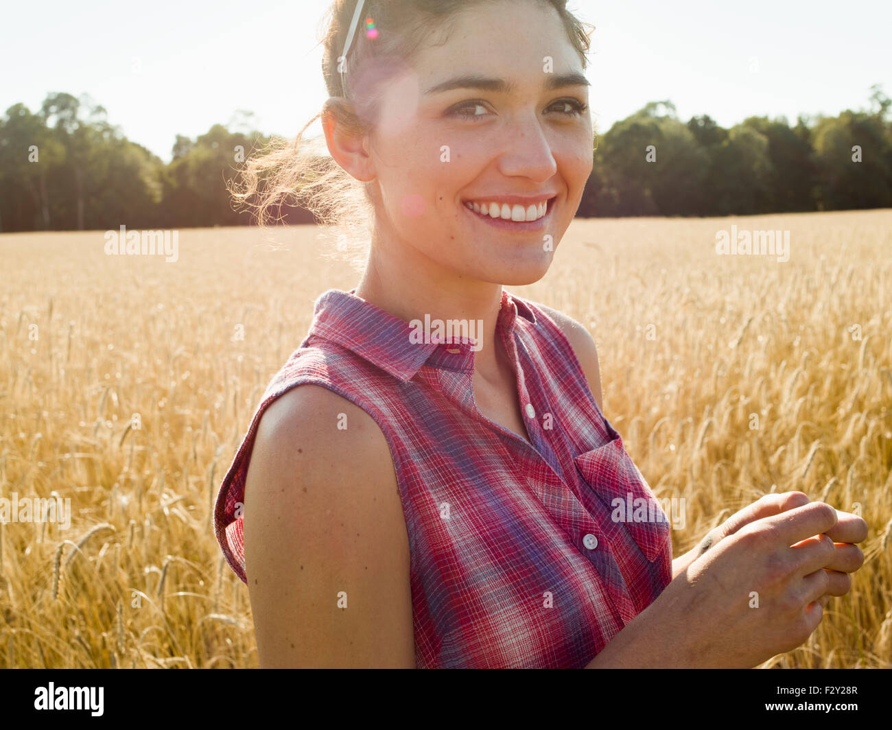 Smiling young woman wearing a checkered shirt standing in a cornfield. - Stock Image