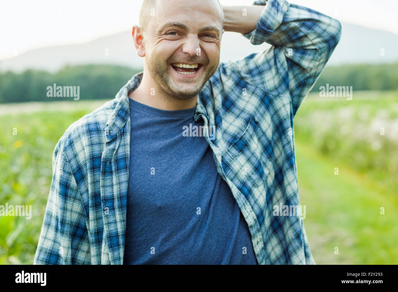 A man outdoors in a wild flower meadow wearing a checked shirt. - Stock Image