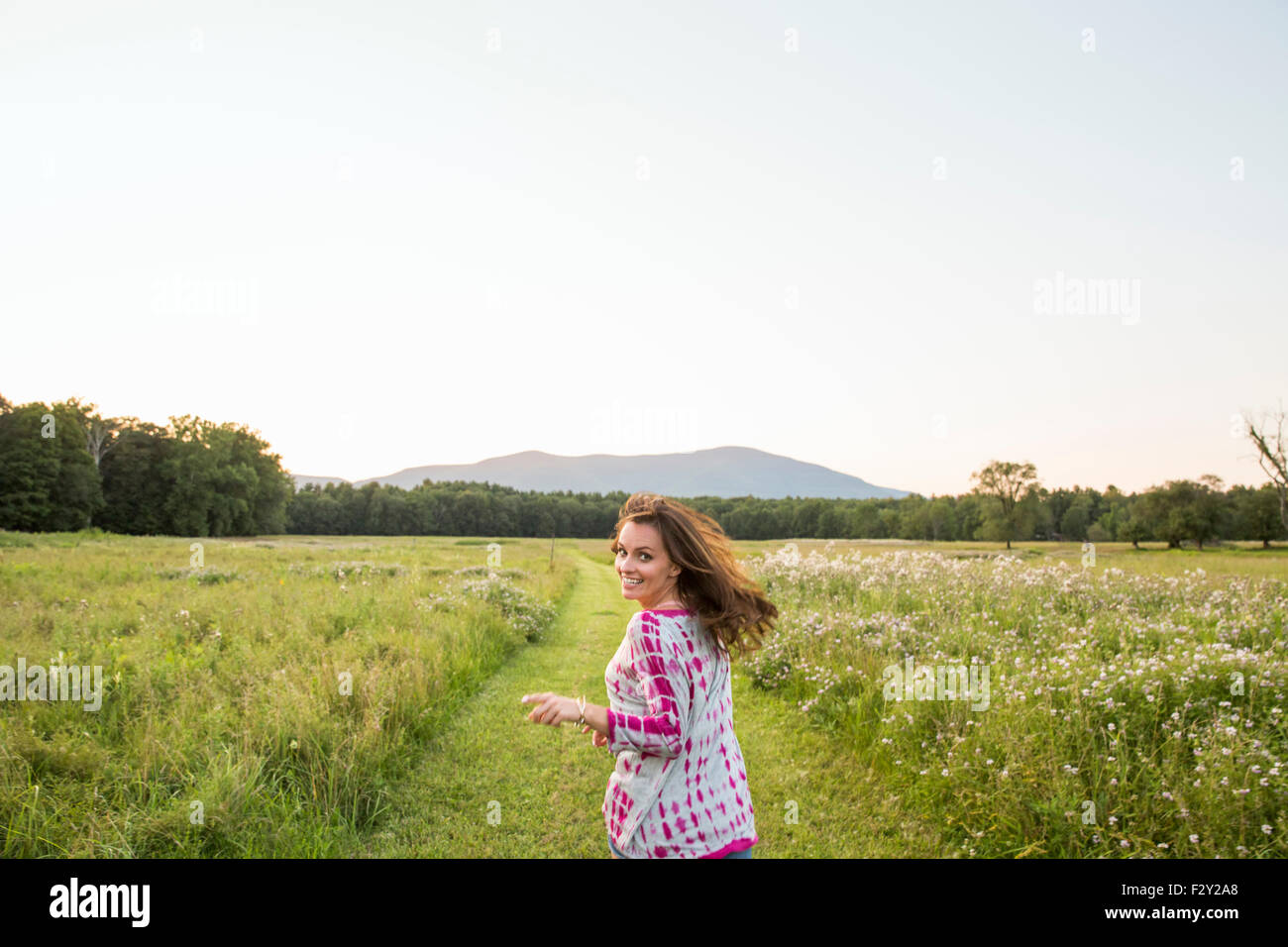 Woman running along a path in a meadow, looking over her shoulder. - Stock Image