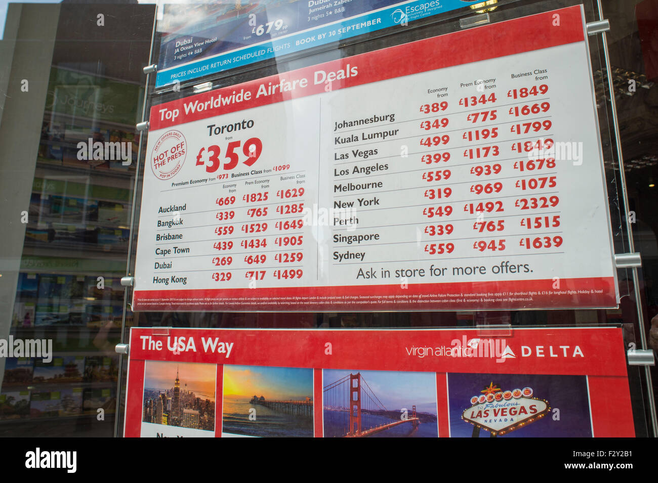 Travel agents window display with flights for sale. - Stock Image