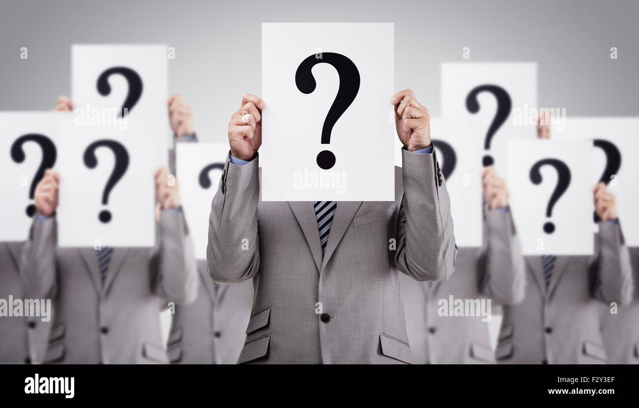 Business colleagues holding question mark signs in front of their faces Stock Photo