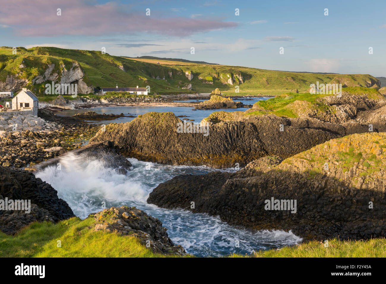 Early morning on the rocks overlooking Ballintoy, County Antrim, Northern Ireland, UK - Stock Image