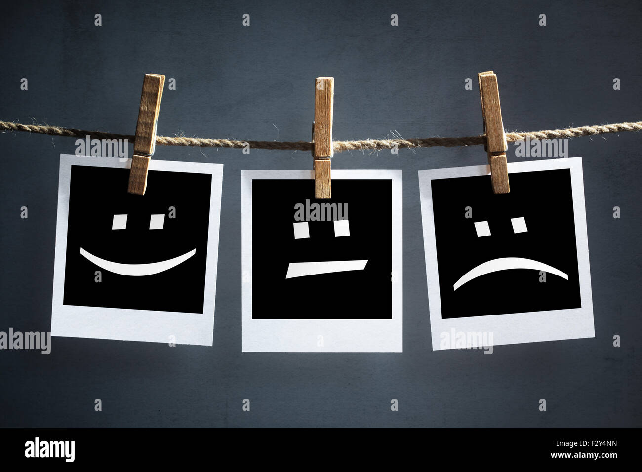 Happy, sad and neutral emoticons on instant print photographs - Stock Image