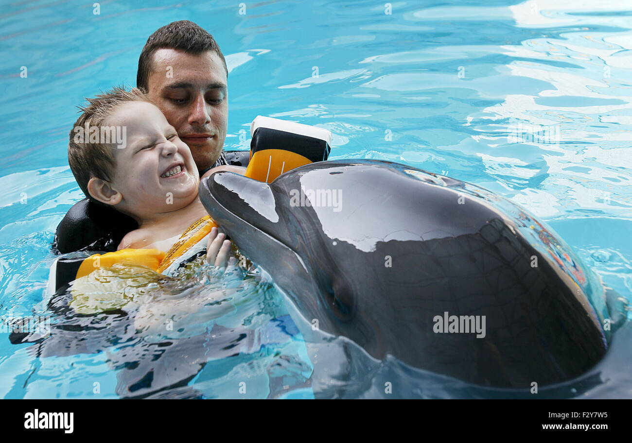 Alushta, Russia. 24th Aug, 2015. A child swimming with a dolphin as part of a therapy in the Akvarel dolphinarium. Stock Photo