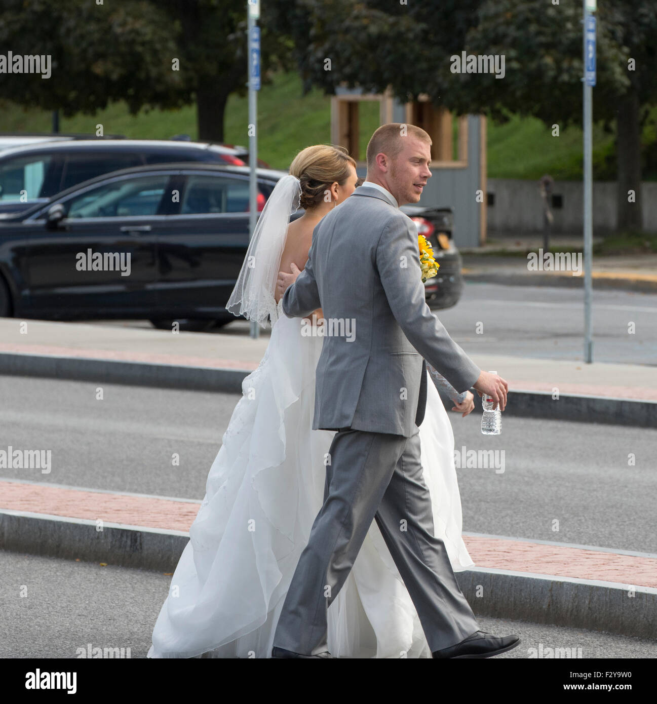 Bride in gown and Groom in tux walking in Lake George New York USA Adirondack State Park on their wedding day. - Stock Image