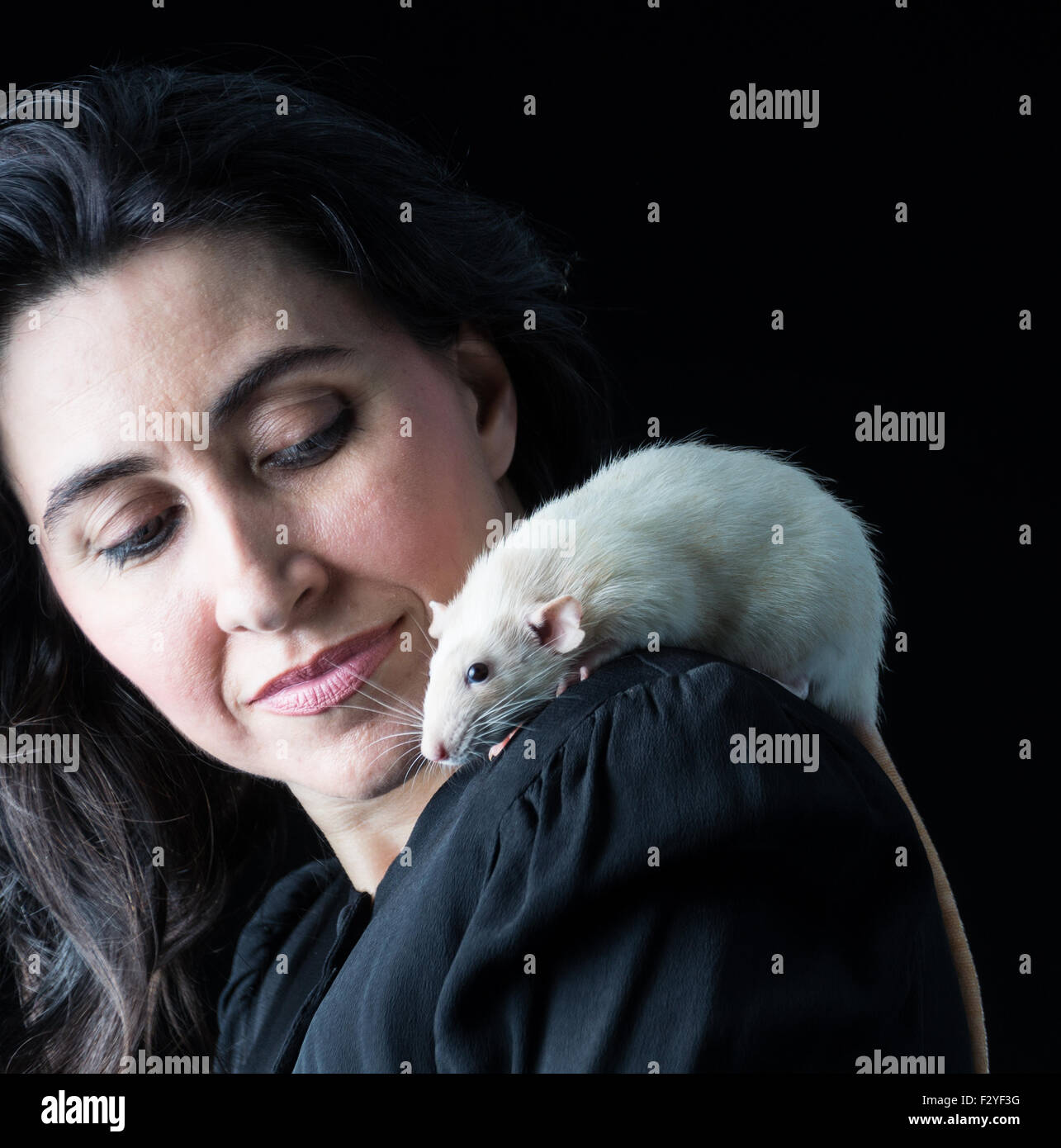 Woman in black standing with white rat on shoulder - Stock Image
