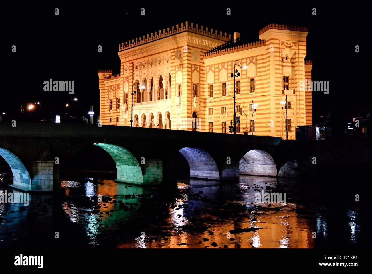 National Library of Bosnia and Herzegovina and river Miljacka in Sarajevo at night. - Stock Image