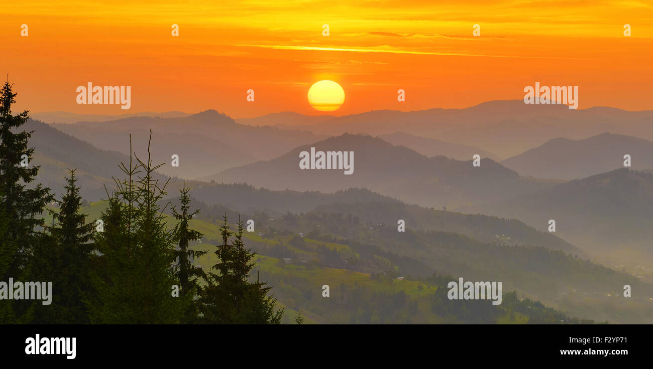 Rising sun above the summer misty mountains. - Stock Image