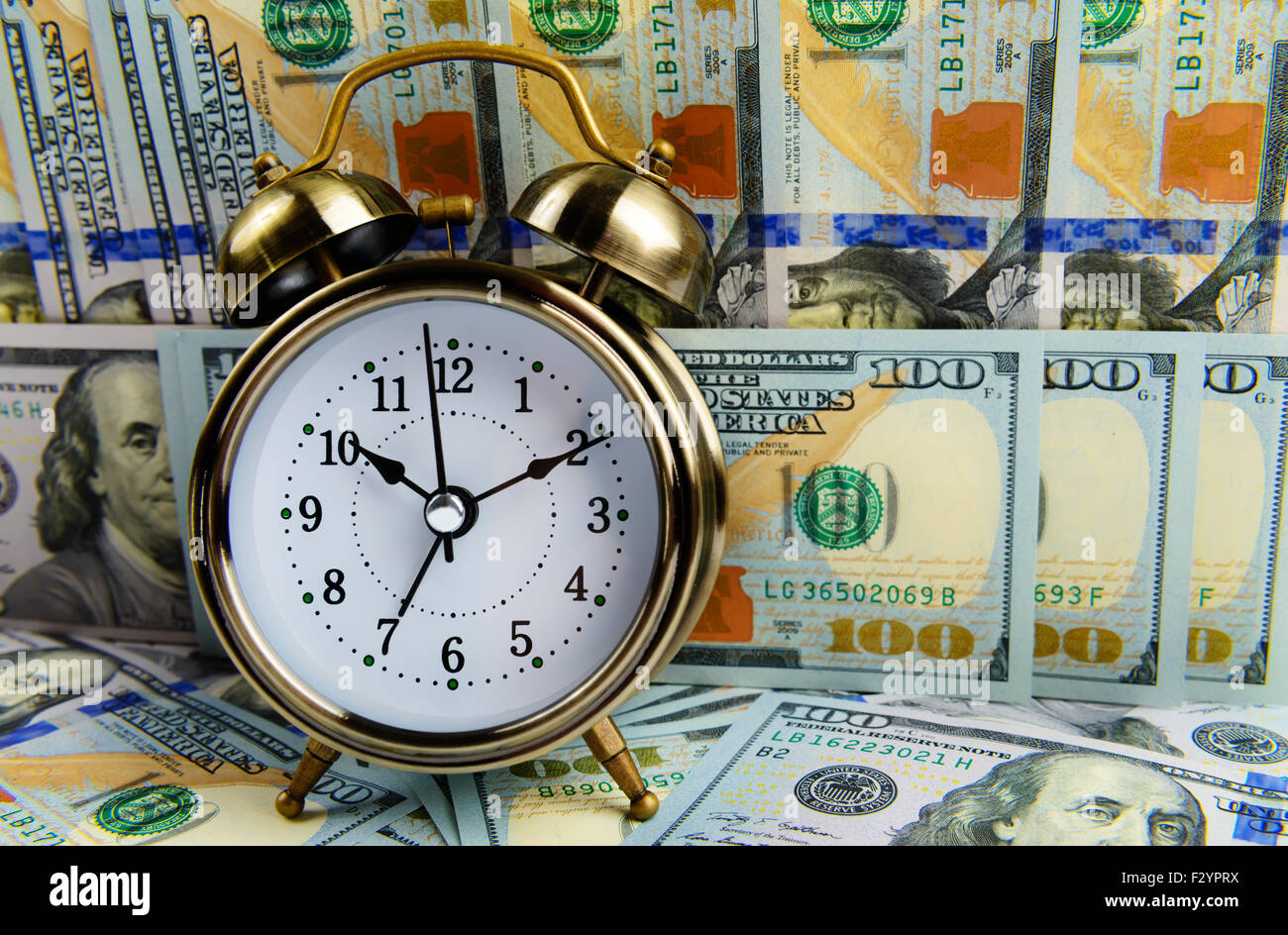 Retro styled alarm clock covered pile of money  Time is money concept - Stock Image