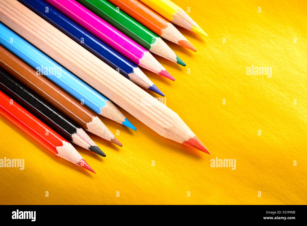 Red pencil standing out from a bunch of colored pencils, leadership concept - Stock Image