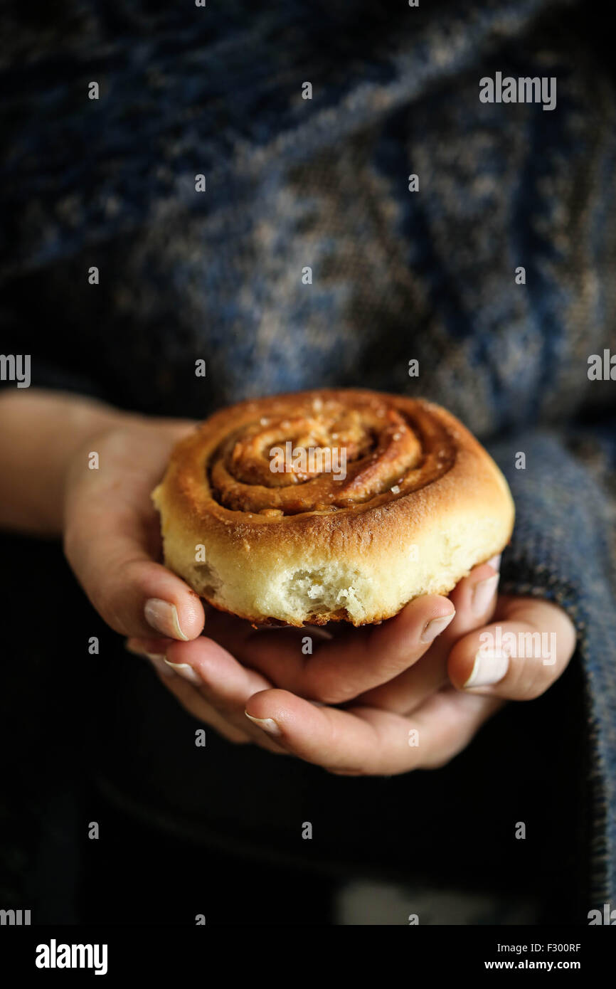 Woman hold a Kanelbullar swedish cinnamon rolls - Stock Image