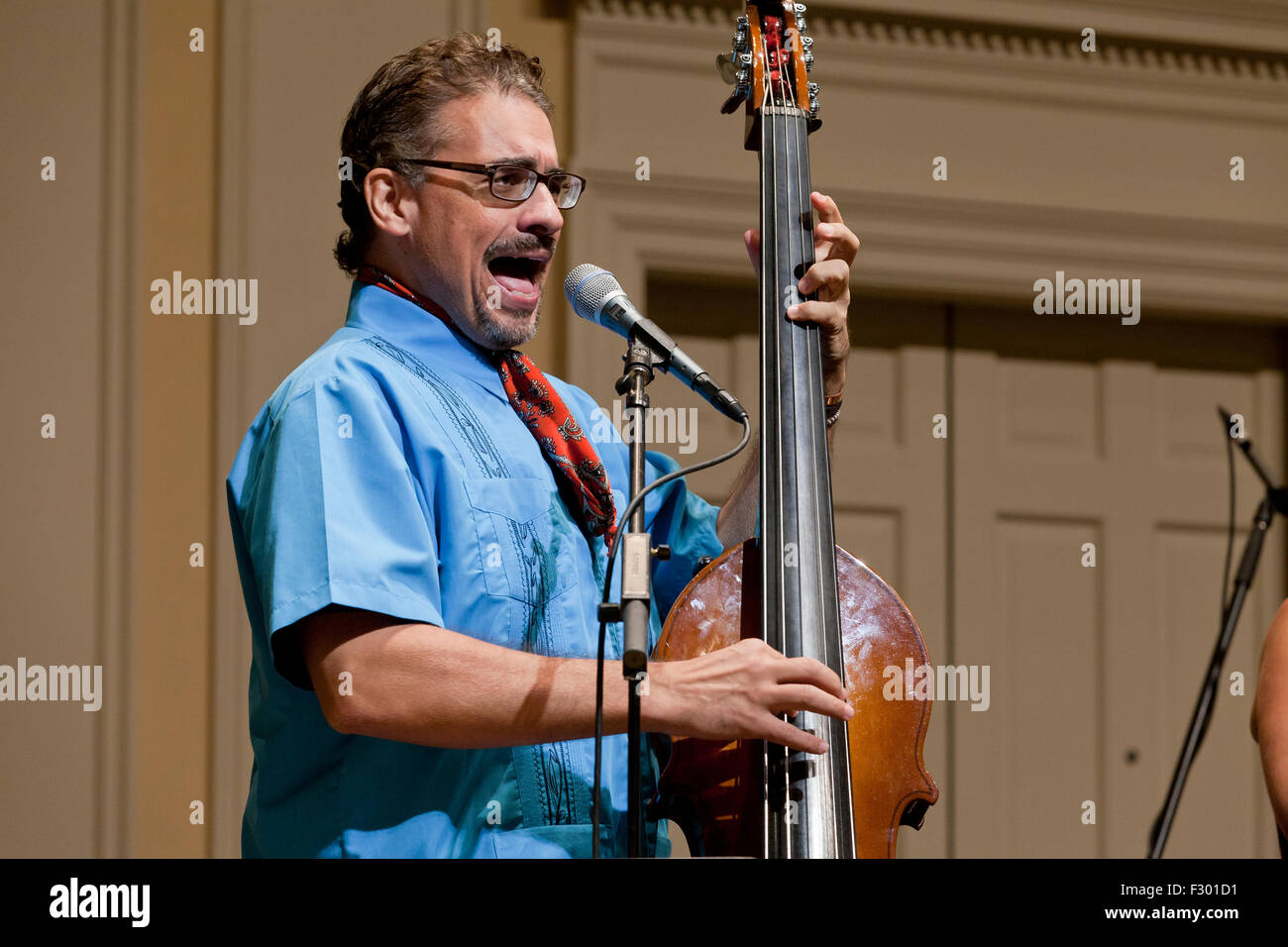 Man singing and playing electric upright Bass instrument on stage - USA Stock Photo