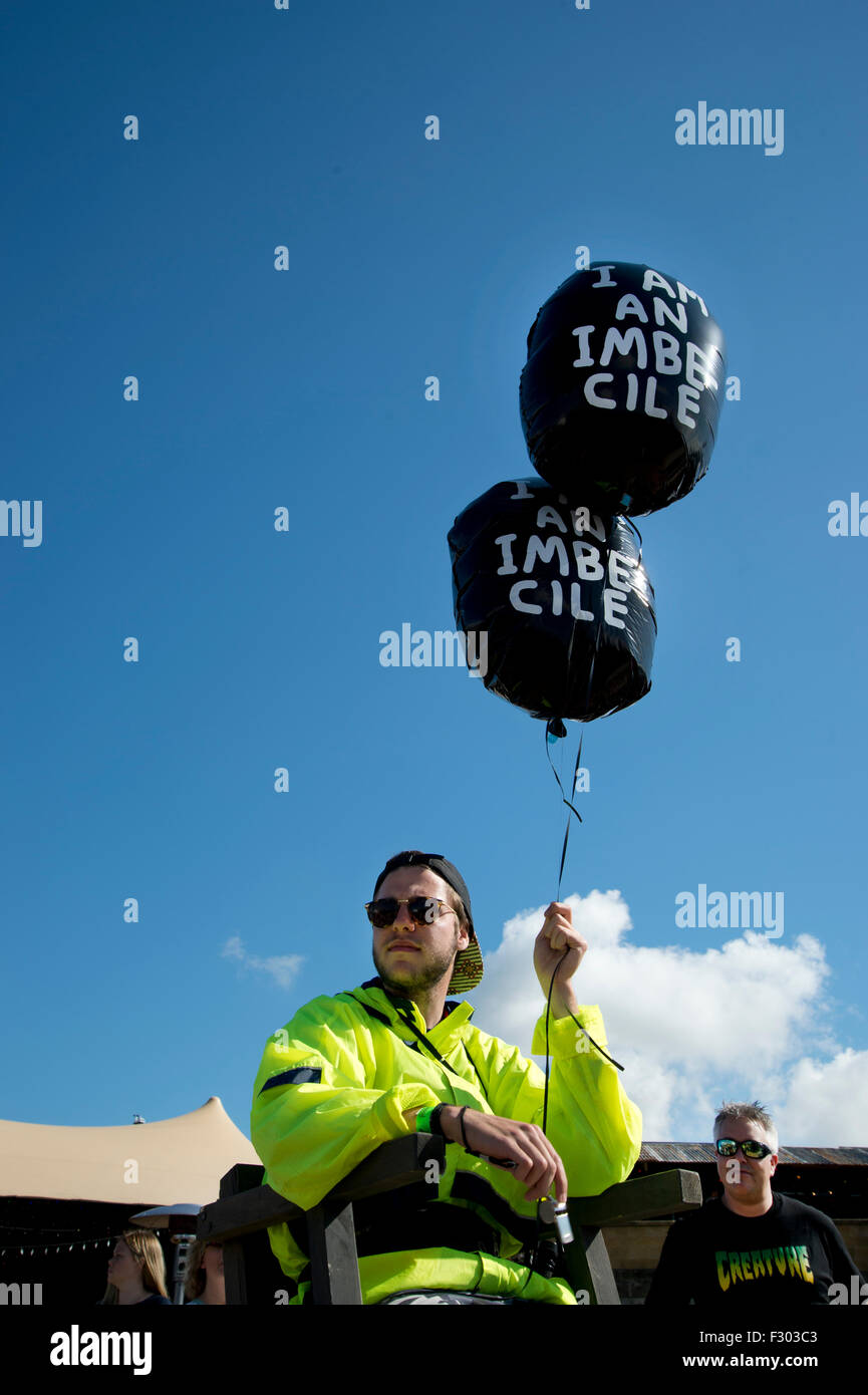 Dismaland, Bemusement Park. Young miserable man selling 'I am an imbecile' balloons, making customers perform - Stock Image