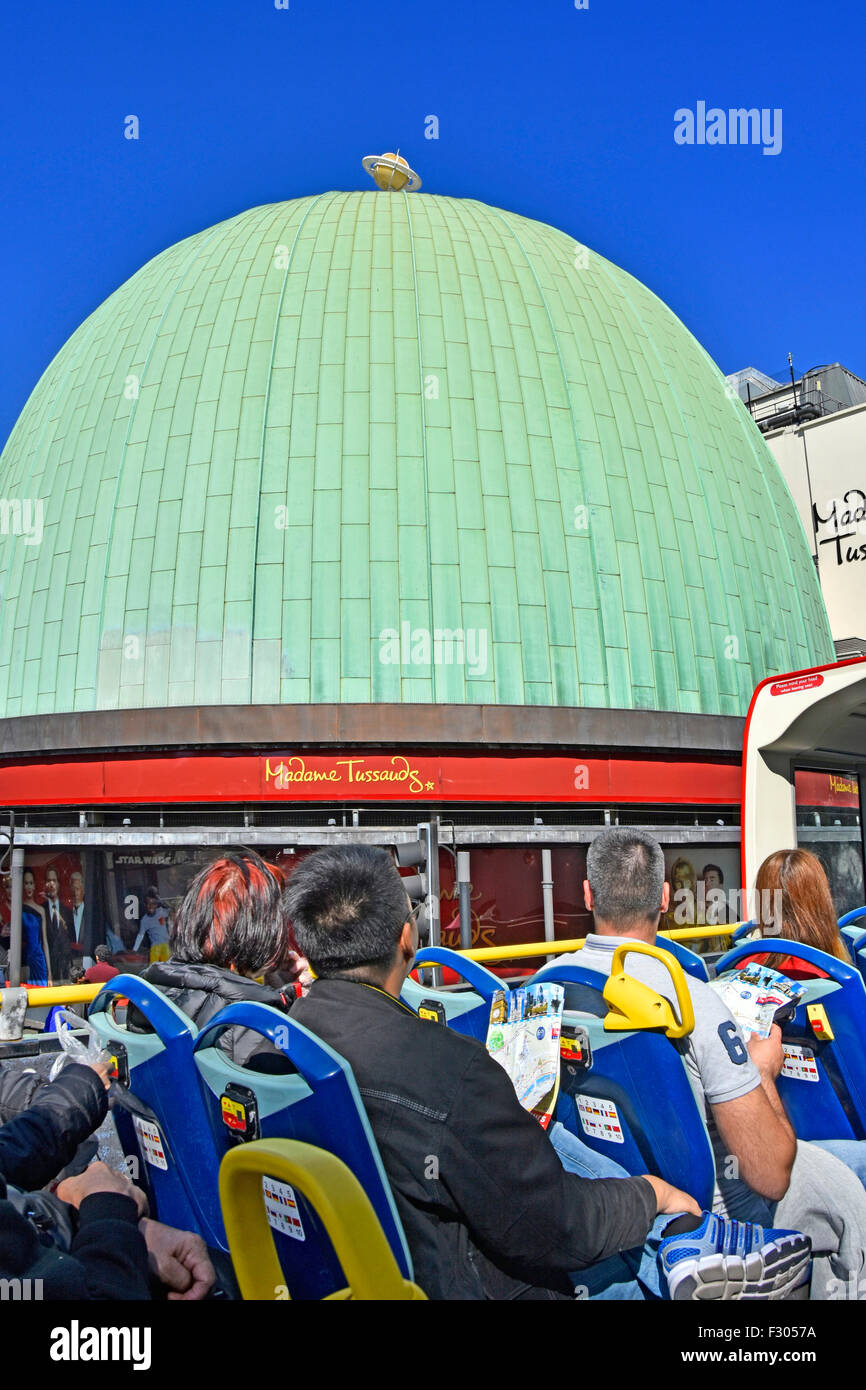 London tourists on top deck of open top sightseeing tour bus passing the copper clad dome of Madame Tussauds England - Stock Image