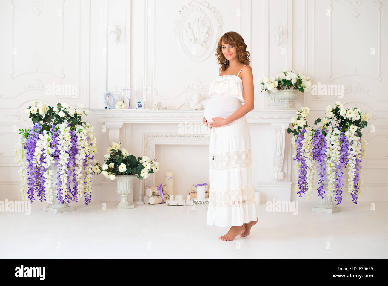 Beautiful pregnant woman in bright clothing in the interior near the fireplace - Stock Image