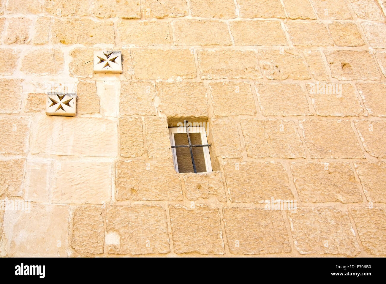 Maltese cross wall decorations and window on old wall in Mdina Stock ...