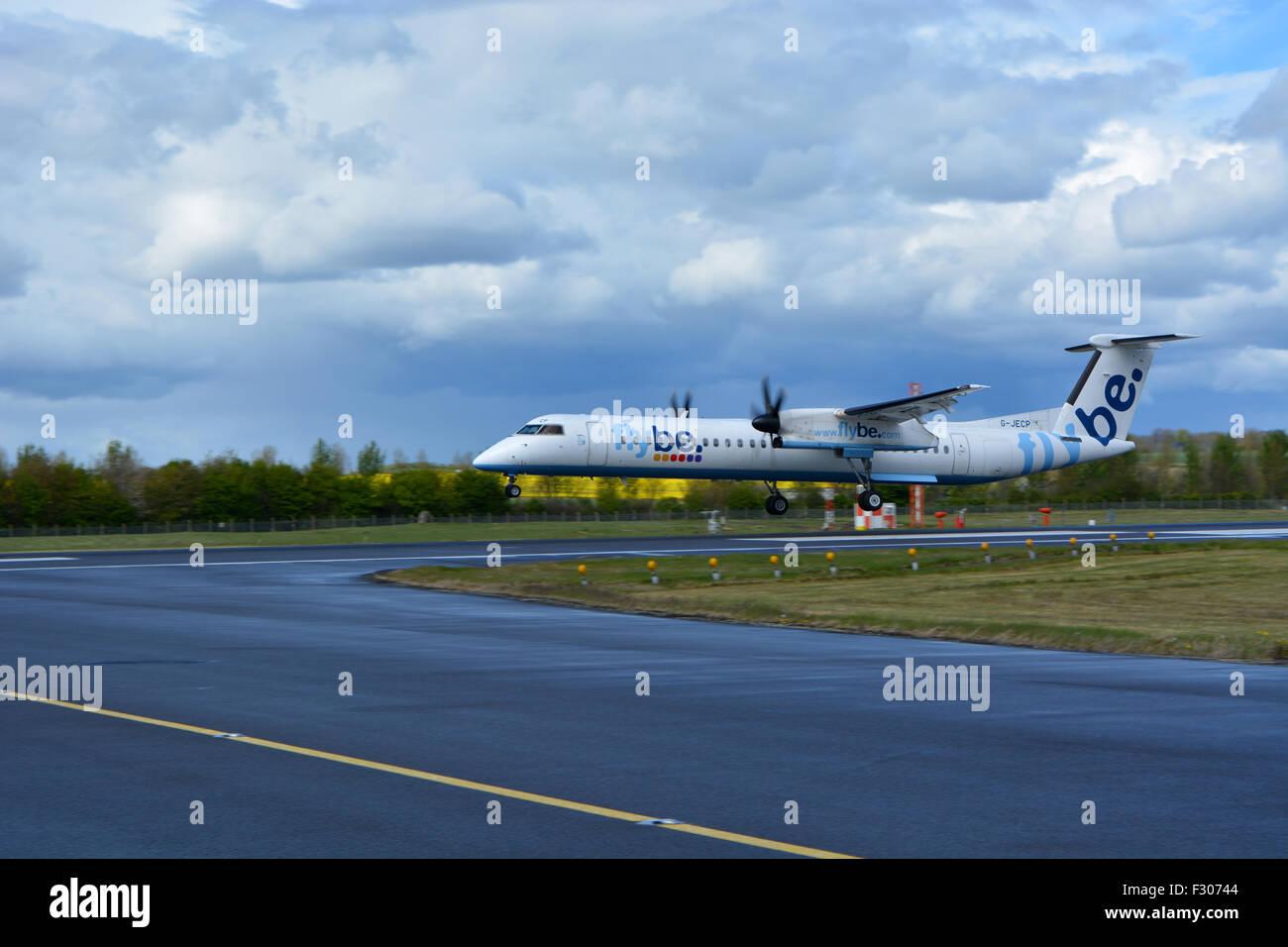 A Flybe Dash 8 Q400 landing on runway 24 at Edinburgh during Summer 2015 arriving from Belfast, UK. - Stock Image
