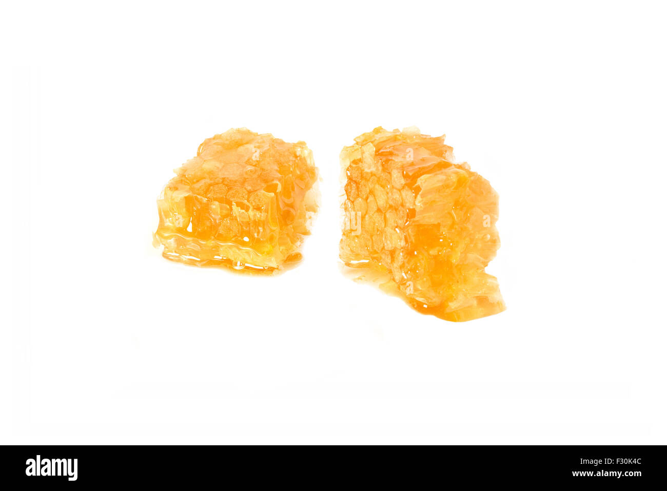 Two honeycomb cubes/ pieces made of fresh greek wild thyme organic honey cutout on white background. Perspective - Stock Image