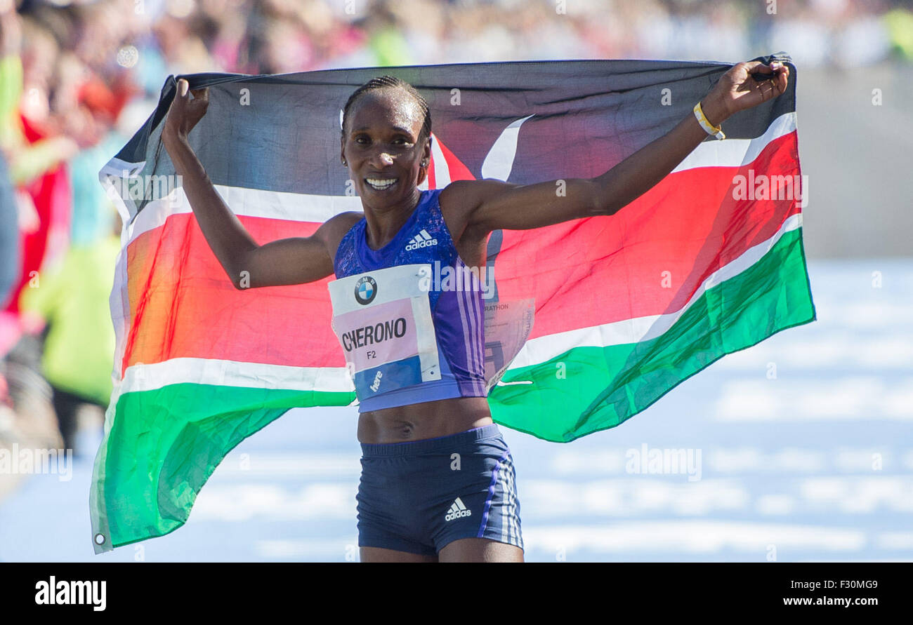 Berlin, Germany. 27th Sep, 2015. Gladys Cherono of Kenya holds the Kenyan flag in her hands and celebrates after Stock Photo