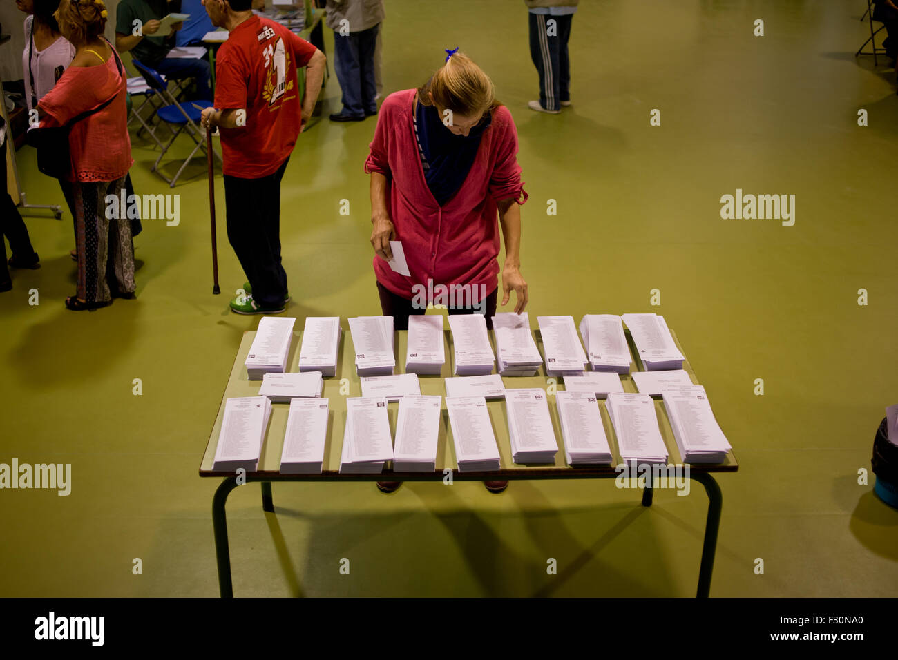Barcelona, Spain. 27th Sep, 2015. A woman looks at ballots in a polling station in Barcelona on 27 Sept. 2015, Spain. - Stock Image