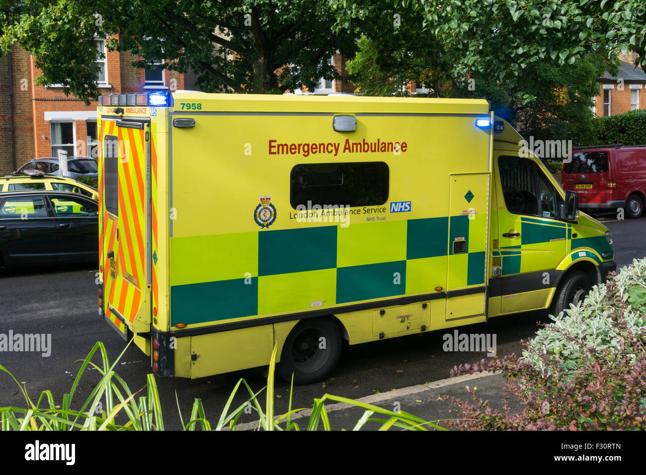 A London Ambulance with blue lights flashing in Bromley, South London. - Stock Image