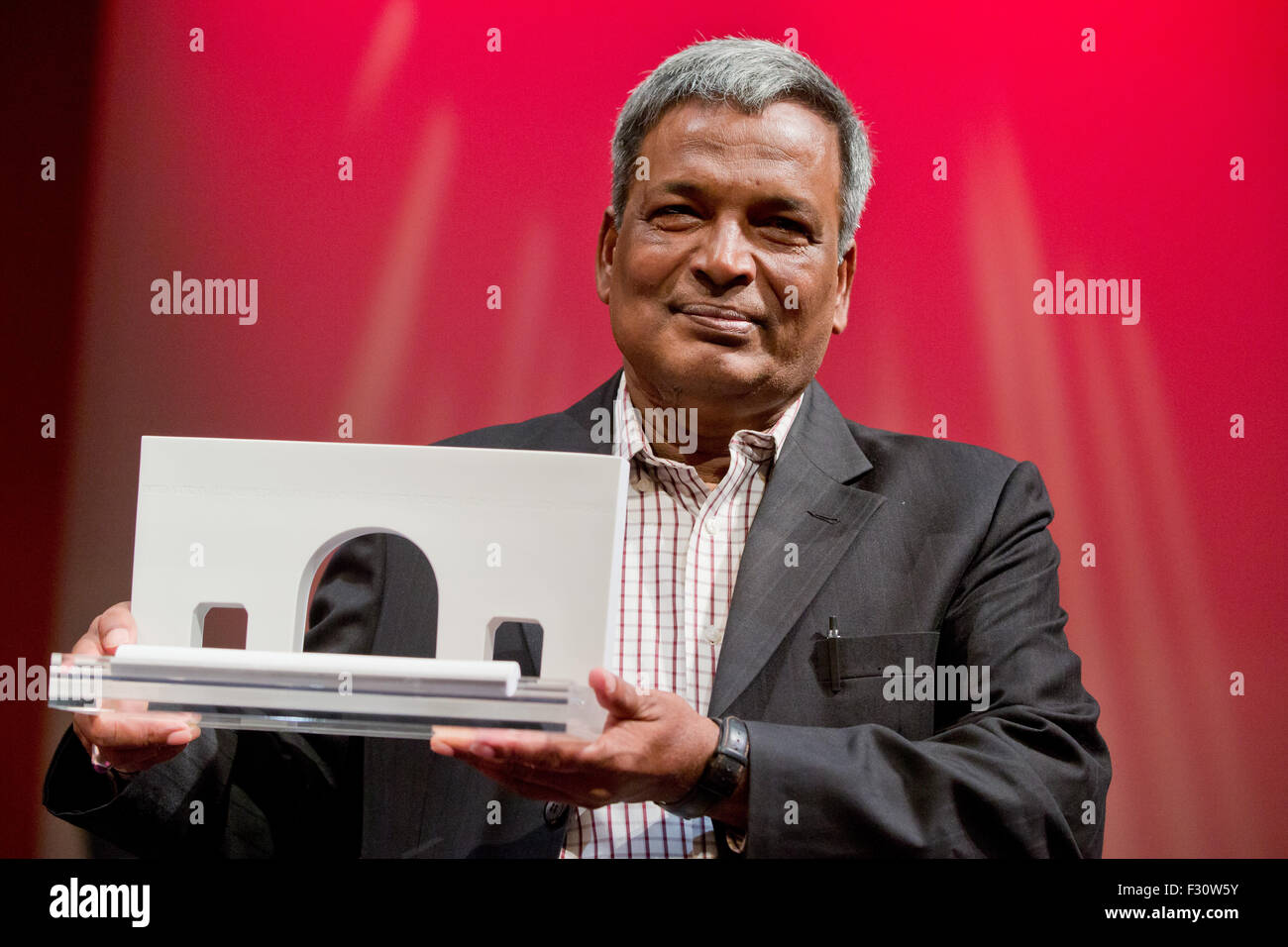 The president of the textile worker's union in Bangladesh, Amirul Haque Amin,  poses with a sculpture which - Stock Image