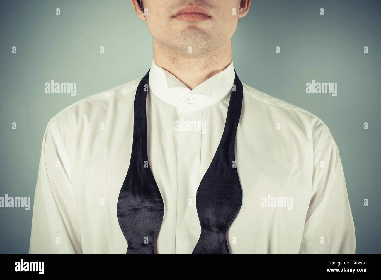 Young man is showing how to tie a formal bow tie - Stock Image