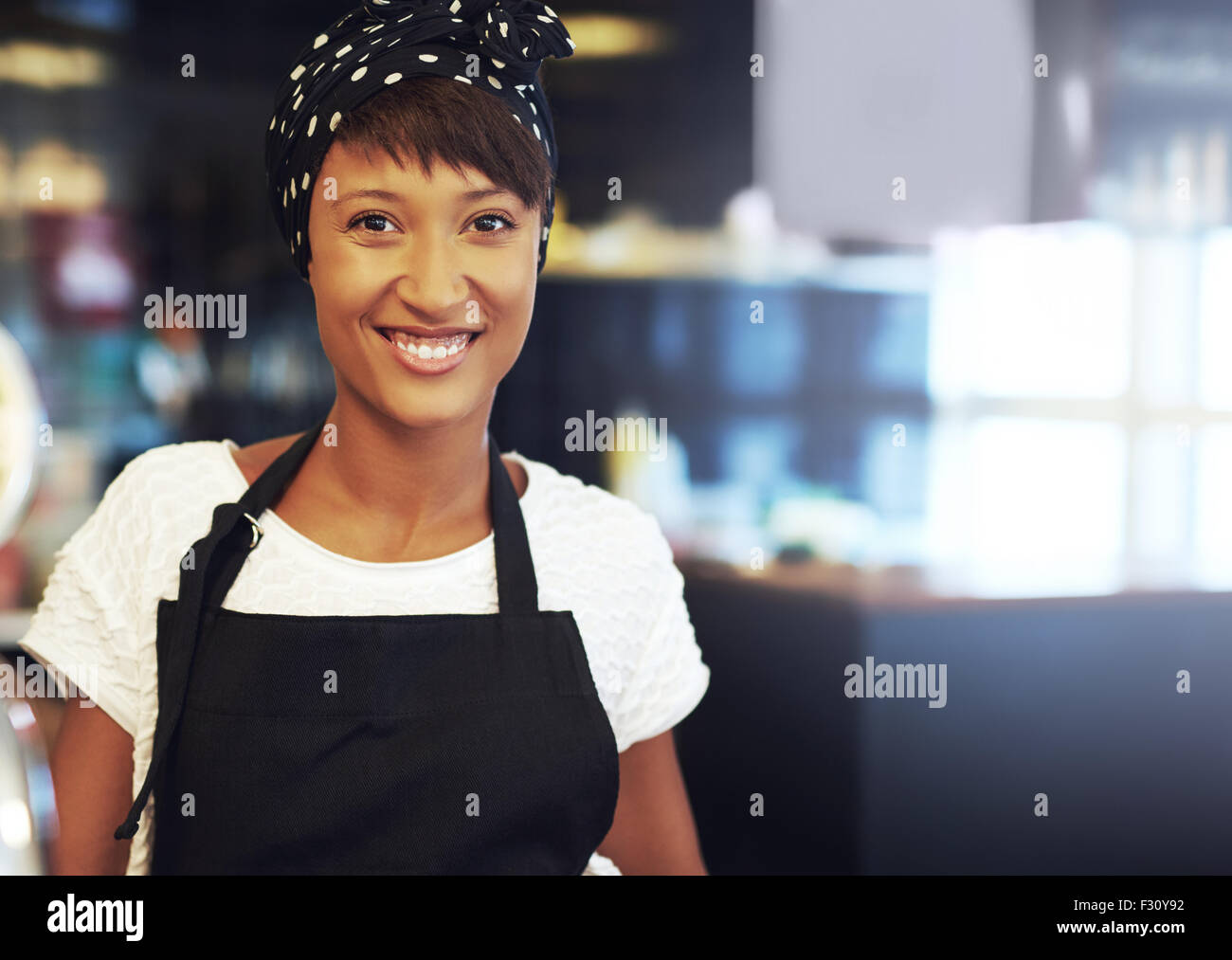 Successful young African American business owner standing in her coffee shop in an apron and bandanna smiling at - Stock Image