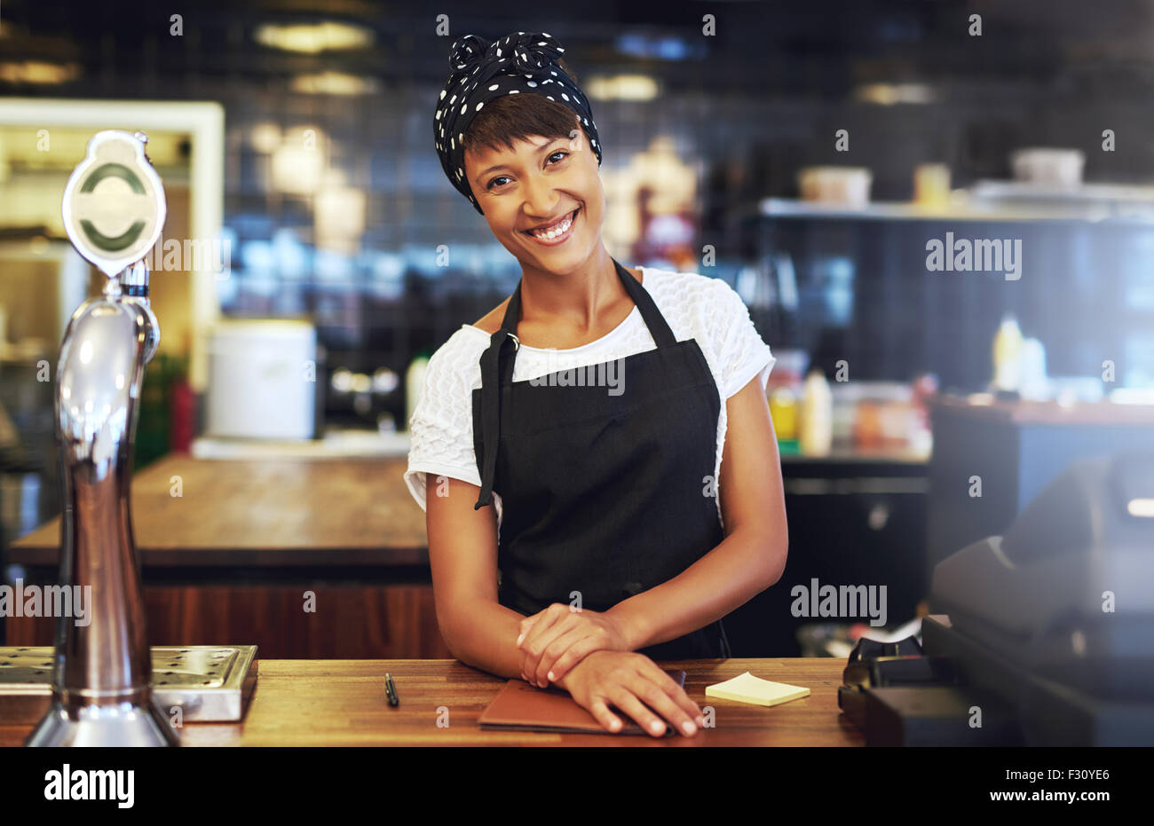Warm welcoming young business entrepreneur standing behind the counter in her cafe giving the camera a beaming smile - Stock Image