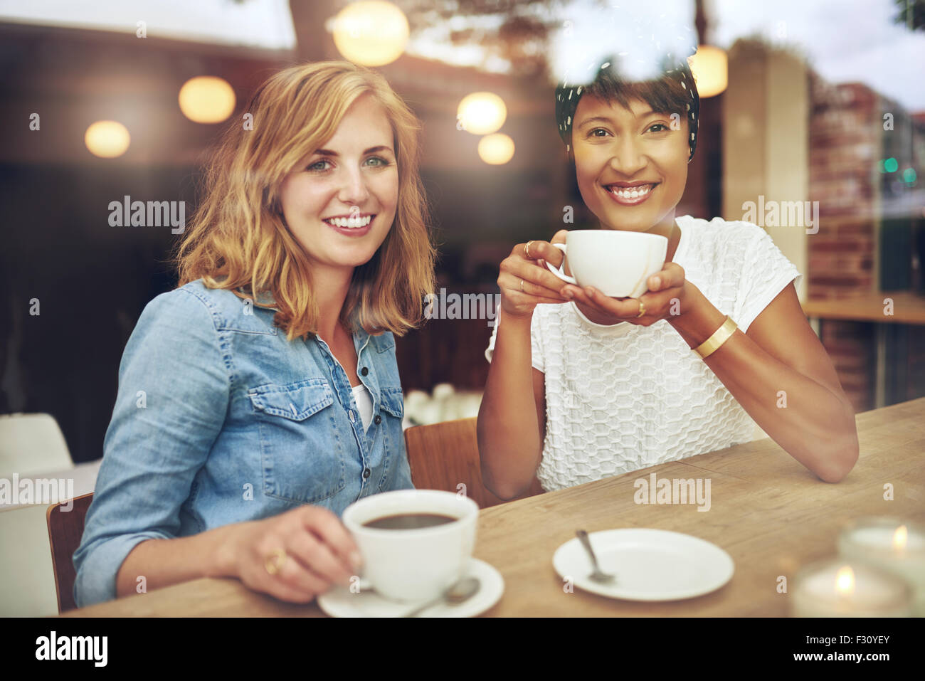 Attractive young multi ethnic female friends sitting together enjoying coffe at a table in a coffee shop smile happily - Stock Image