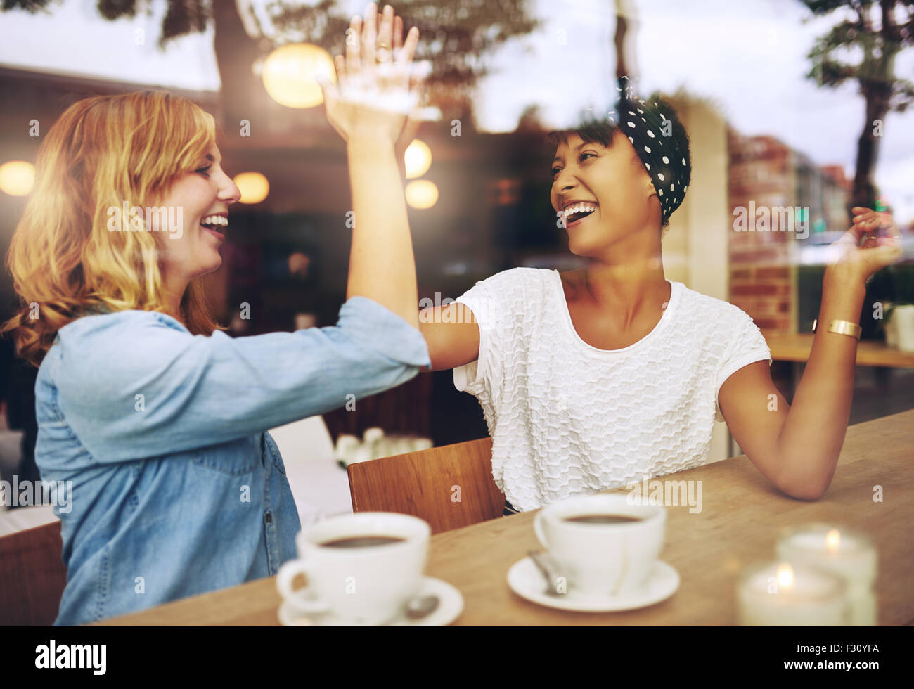 Happy exuberant young girl friends giving a high five slapping each others hand in congratulations as they sit together - Stock Image