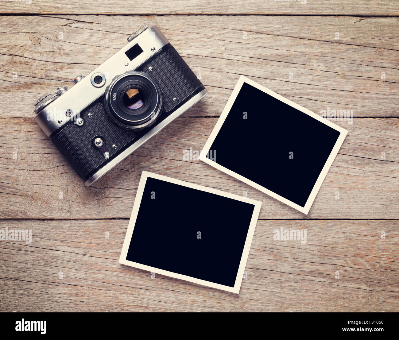 Vintage film camera and two blank photo frames on wooden table. Top ...