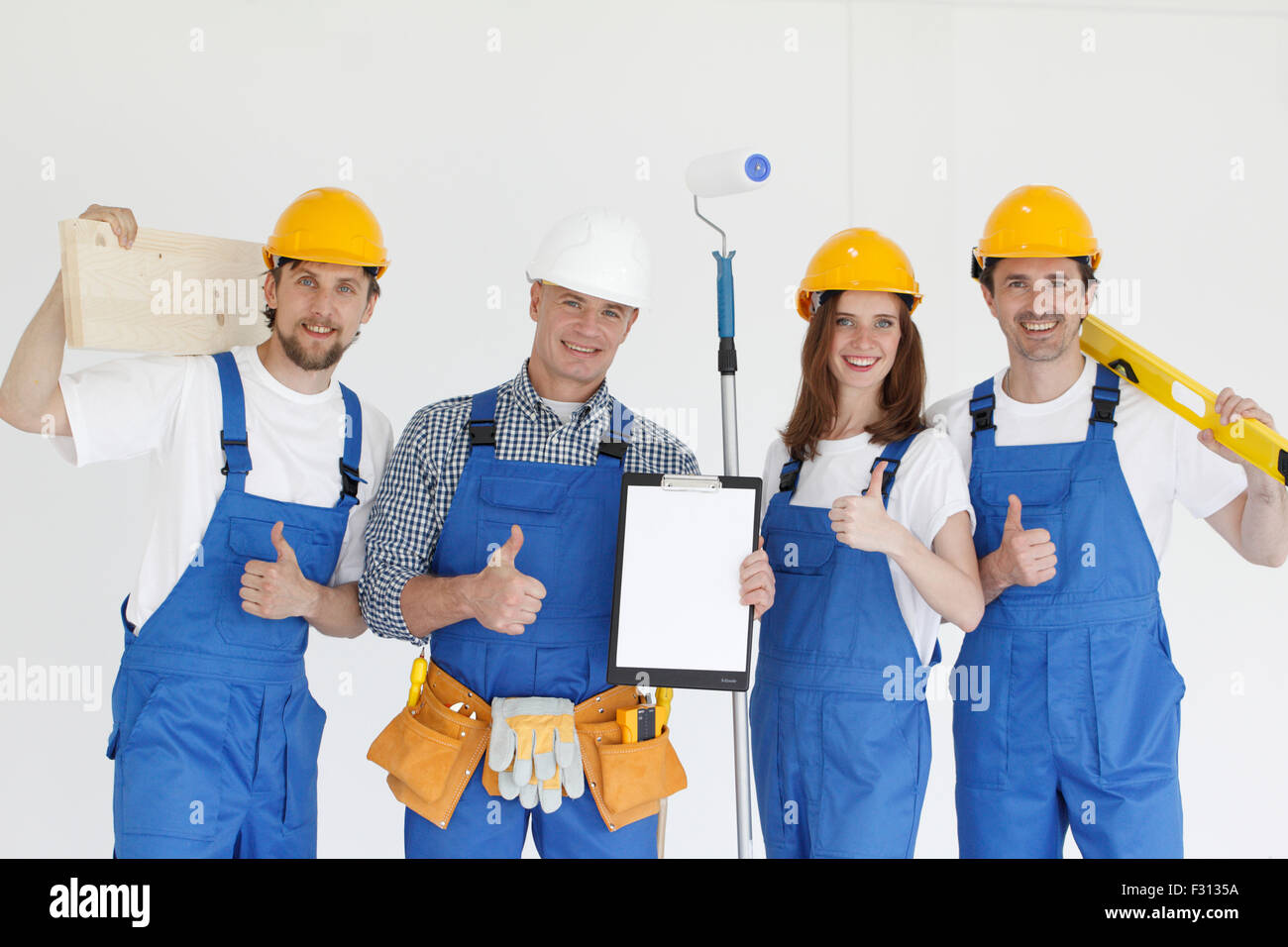 Group of smiling builders in hardhats with tools indoors - Stock Image