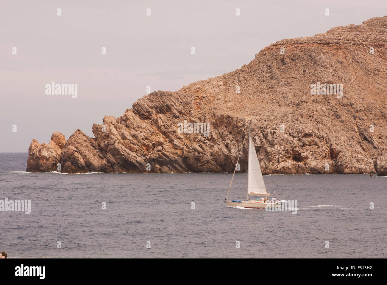 sailing boat passes cliffs in Minorca - Stock Image