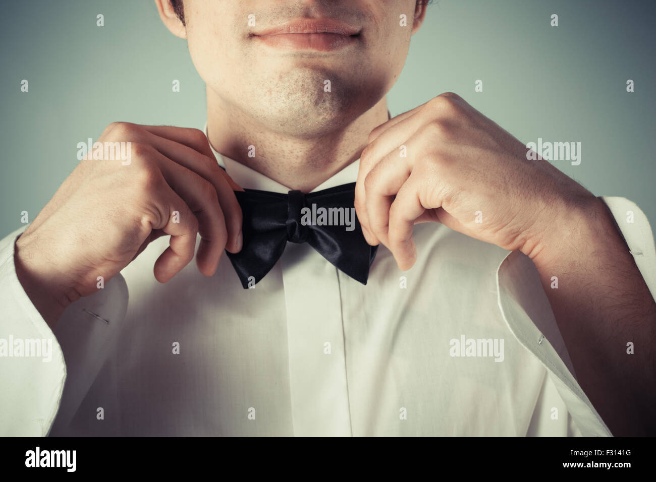 Closeup on a happy young man tying a bow tie - Stock Image