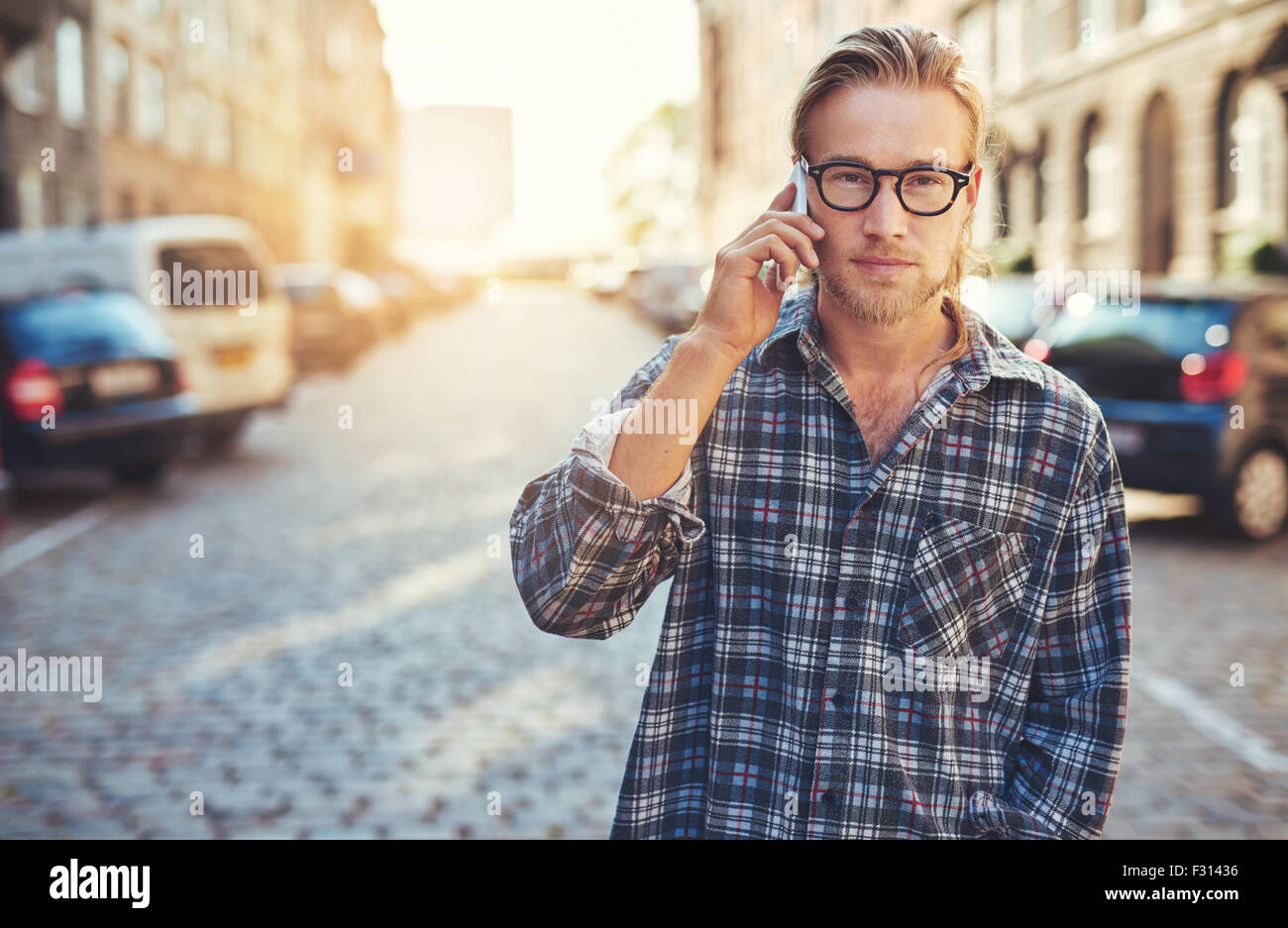 closeup portrait of young man talking on his cellphone in the city - Stock Image