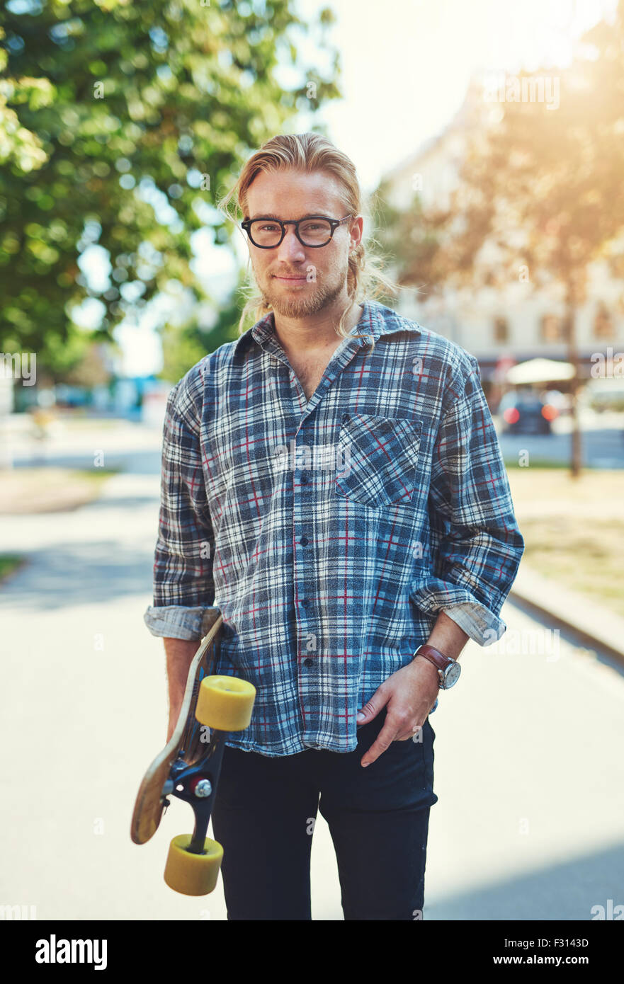 Portrait of cool young man with long hair and glasses carrying a skateboard - Stock Image