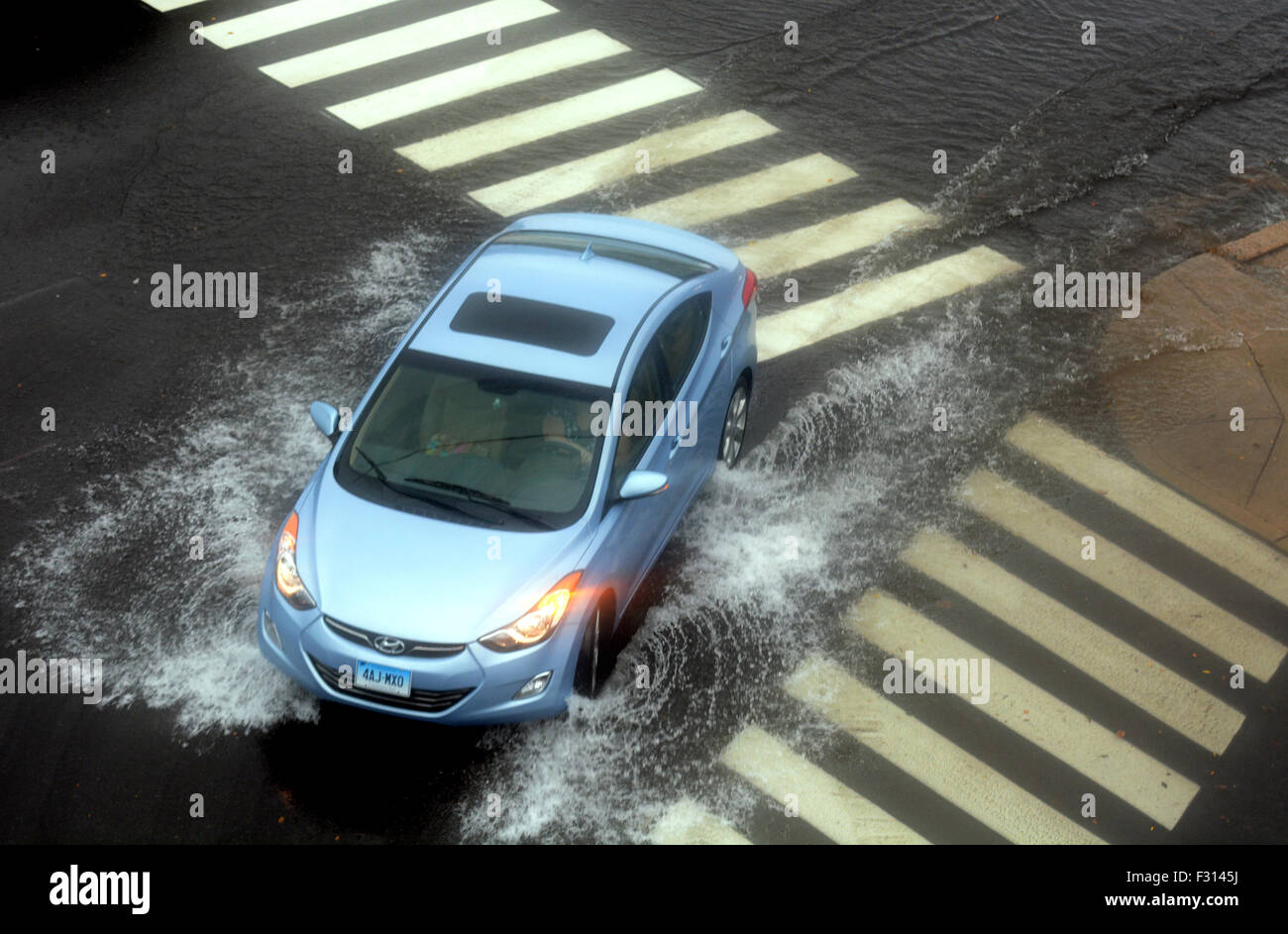A car turns up Market Street in Norwich on Thursday as heavy rain falls though out the state. - Stock Image
