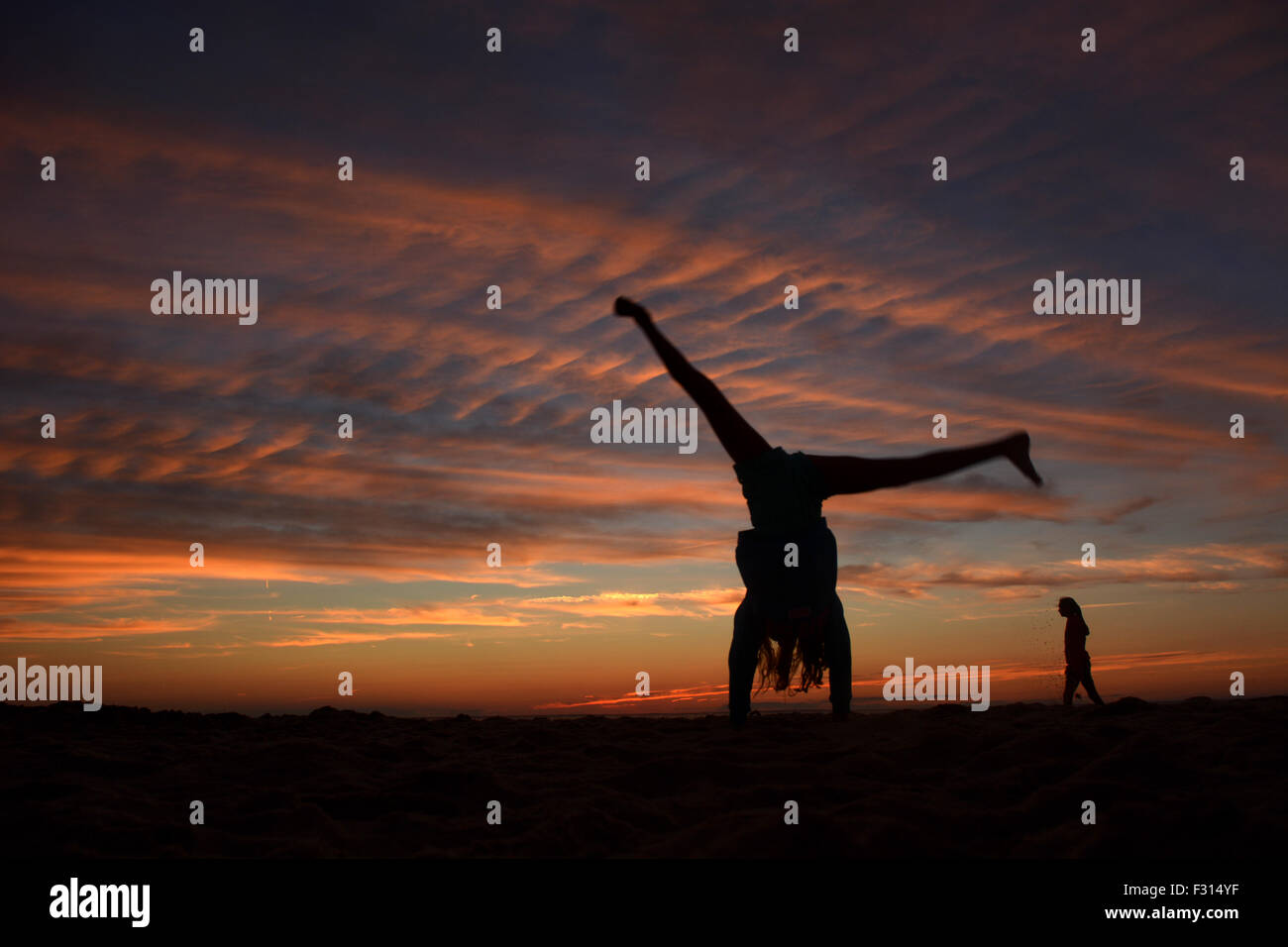 Children silhouette as they jump and enjoy the sunset - Stock Image