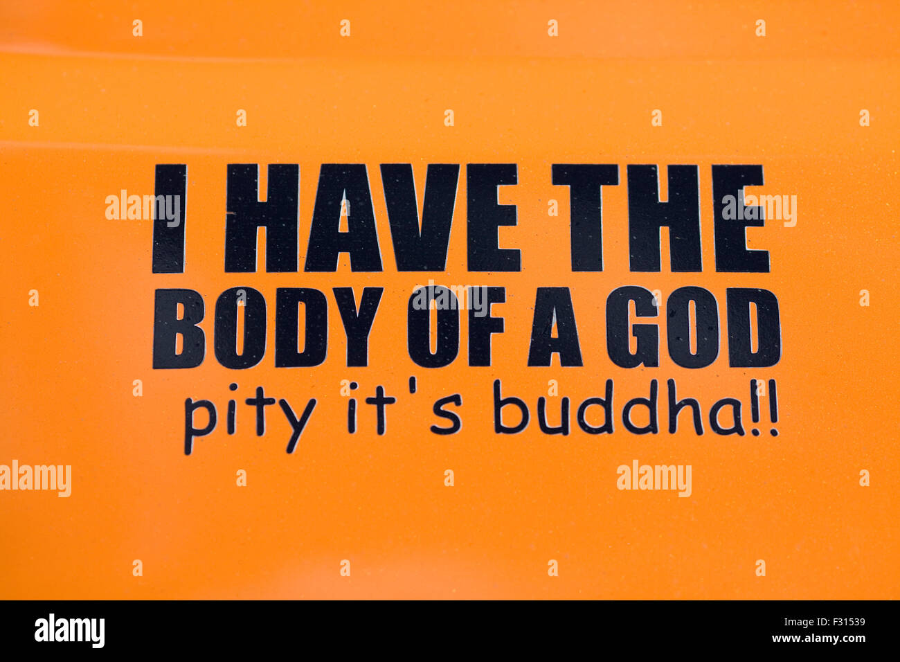 I have the body of a god Pity its Buddha Orange and black Sign - Stock Image