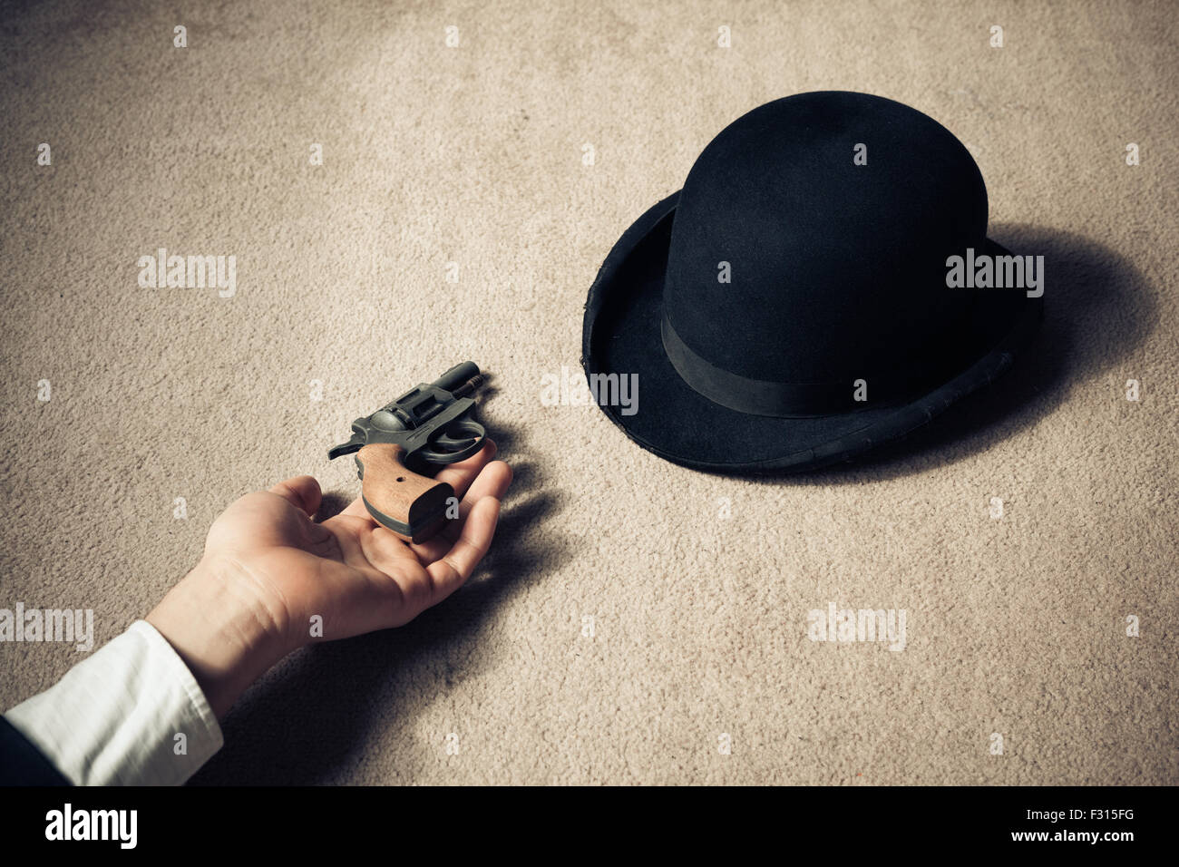 A man is lying dead on the floor with his hat and his revolver - Stock Image