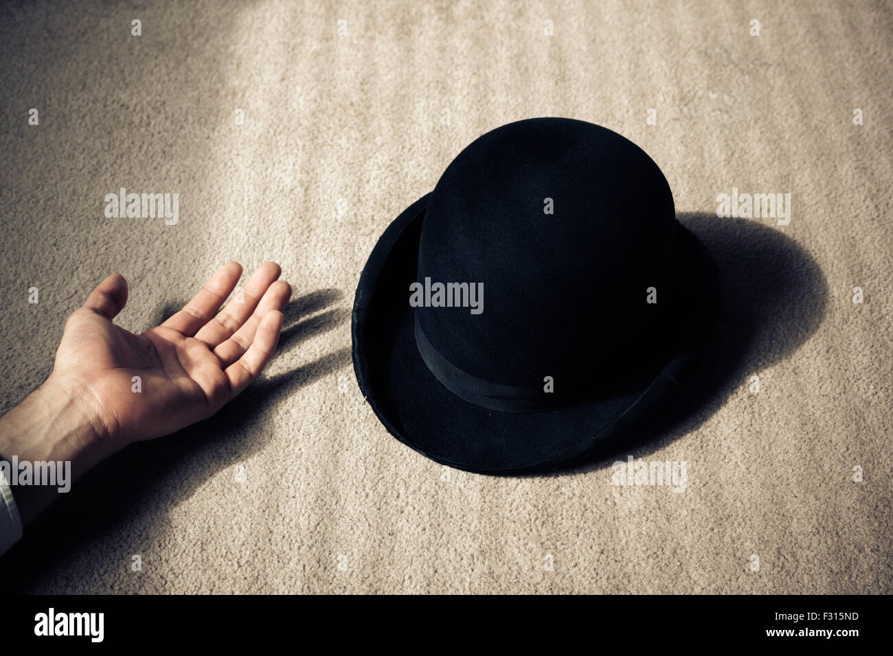 A man is lying dead on the floor with his hat next to him - Stock Image